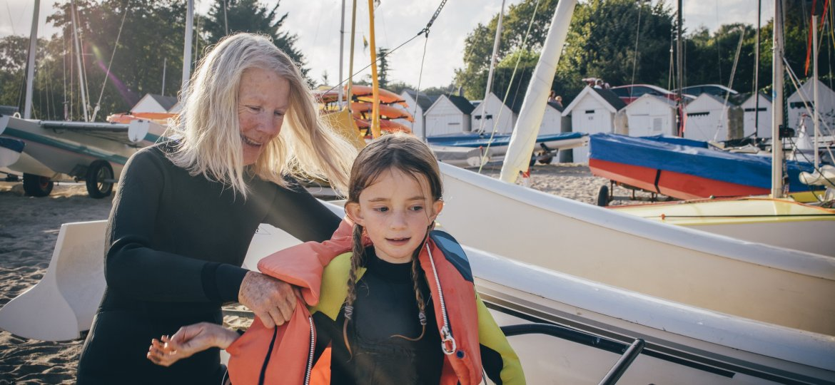 Grandmother Assists Child with Lifejacket