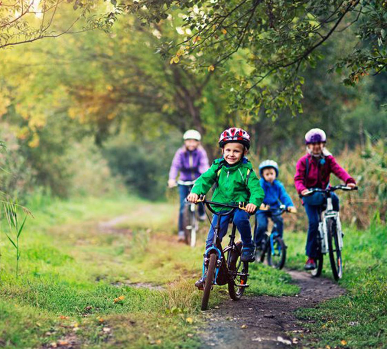 Family biking with helmets on