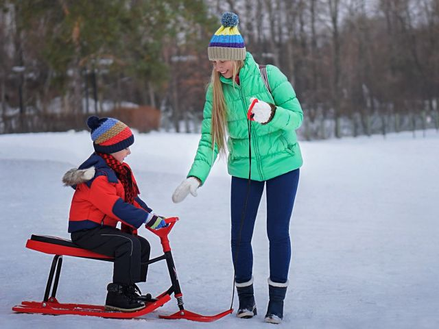 shows a women and boy on a sled